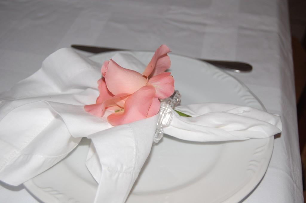 Detalhe da mesa do almoço com porta guardanapo feito com rosa natural.
