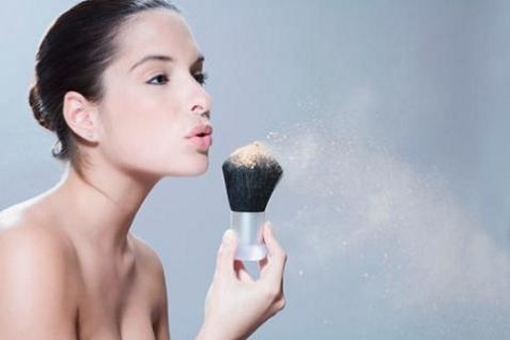 Young woman blowing powder from make-up brush, close-up, side view