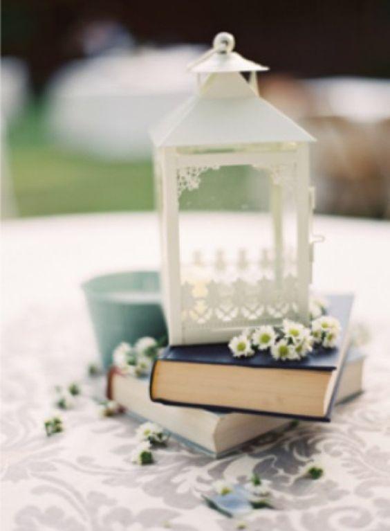 Decoração de mesa de bolo com livros, lanternas e flores, por Alessandra Faria